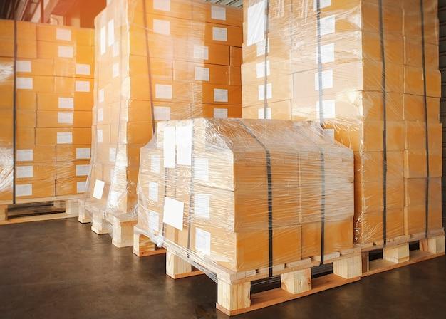 Mit kunststoff umwickelte verpackungskartons auf paletten in versandkartons des lagerhauses