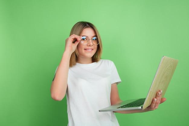 Mit laptop emotional. kaukasisches porträt der jungen frau lokalisiert auf grüner wand. schönes weibliches modell im weißen hemd.