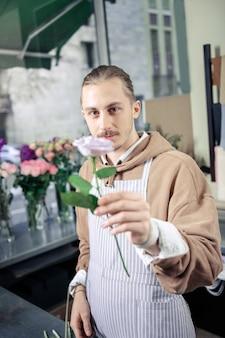 Mit liebe. erfreulicher florist, der lächeln auf gesicht hält, während er kamera betrachtet