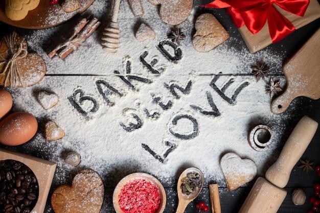 Mit liebe gebacken auf mehl geschrieben. lebkuchenherz geformte kekse, gewürze, kaffeebohnen und backzubehör auf schwarzem holzhintergrund