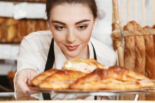 Mit liebe gemacht. schöne junge bäckerin, die frisch gebackene croissants zum schaufenster setzt