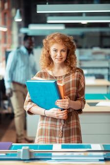 Mit lockigem haar. schöne rothaarige frau mit lockigem haar, die bücher hält, die im verlagsbüro stehen
