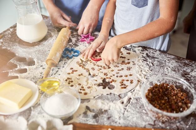 Mit mehl bedeckte kinder machen aus teig keksformen