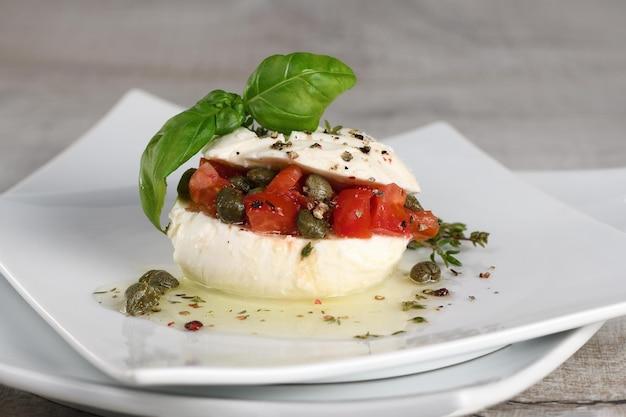 Mit mozzarella gefüllte tomaten mit kapern, gewürzen und basilikum in öl