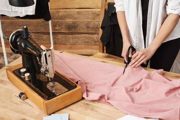 Mit mühe wird es passieren. beschnittener schuss von weiblichem schneider, der stoff schneidet, während er an neuer kleidungslinie für ihr geschäft in werkstatt arbeitet, mit nähmaschine und schere während der arbeit.