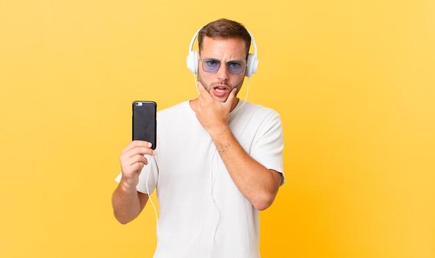 Mit mund und augen weit geöffnet und hand am kinn, musik hören mit kopfhörer und smartphone