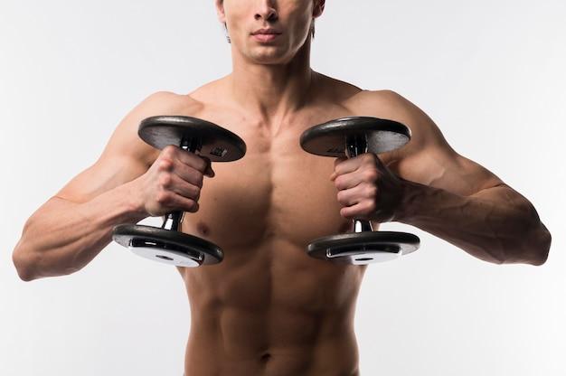 Mit nacktem oberkörper muskulöser mann, der gewichte hält