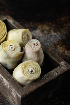 Mit olivenöl marinierte artischockenherzen auf altem rustikalem tisch