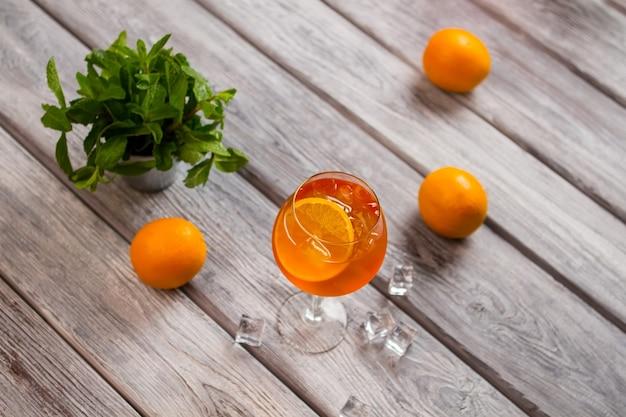 Mit orangenscheibe trinken. orangen auf holzoberfläche. aperol-spritz mit sekt. duftende minze in kleinem eimer.