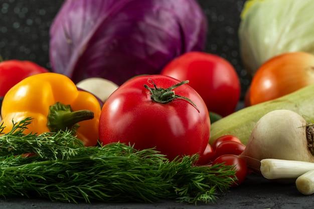 Mit paprika-vitaminen angereichertes salatgemüse einschließlich tomate und purpurkohl auf dunklem hintergrund