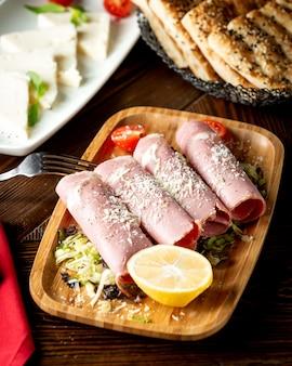 Mit parmesan und zitronenhälfte garnierte salamiröllchen