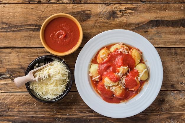 Mit pesto gefüllte gnocchi mit hausgemachter tomatensauce und käse