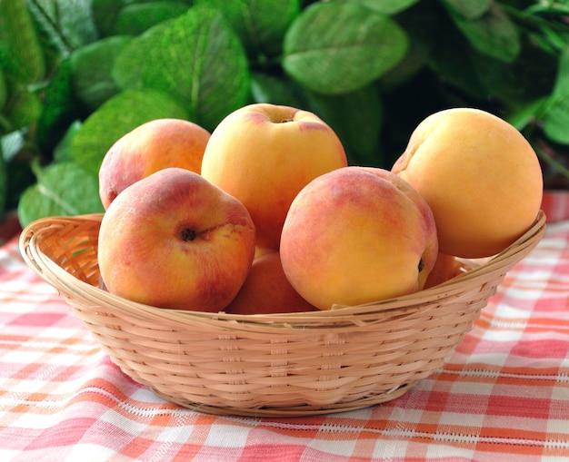 Mit pfirsichen in einem weidenkorb auf der tischdecke, auf einem hintergrund von laub