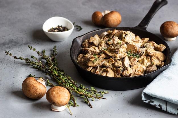 Mit pilz und thymian gedünstetes fleisch in einer gusseisernen pfanne