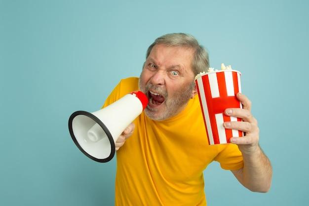 Mit popcorn in mundfrieden rufen. kaukasisches mannporträt auf gelbem studiohintergrund. schönes männliches modell im gelben hemd.