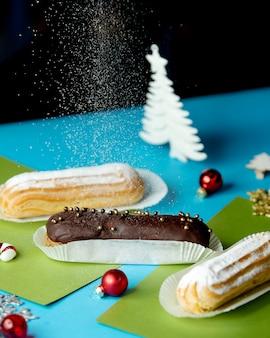 Mit puderzucker bestreute schokoladen- und vanille-eclairs
