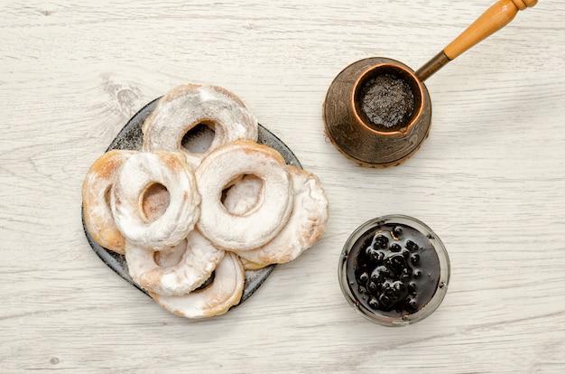 Mit puderzucker, frischem kaffee und marmelade bestreute donuts auf hellem holzfone. ansicht von oben