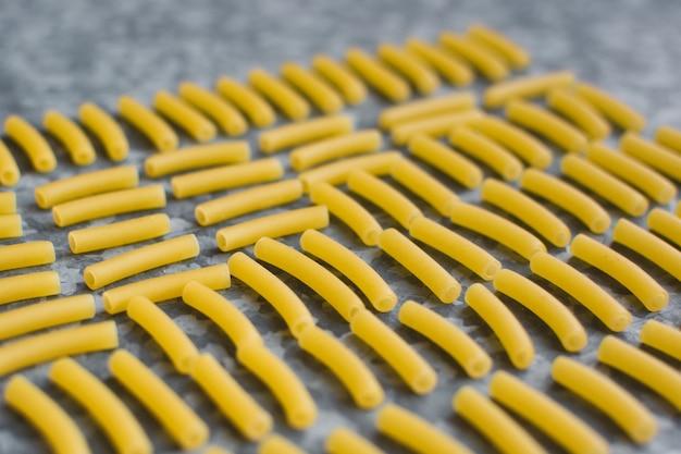 Mit rohem teigwarenmakkaroni auf einem metallischen hintergrund spielen
