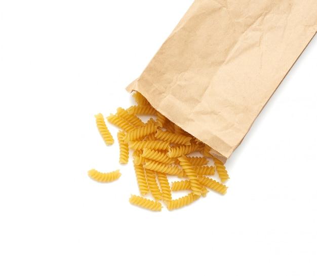 Mit rohen fusilli-nudeln aus brauner papiertüte bestreut