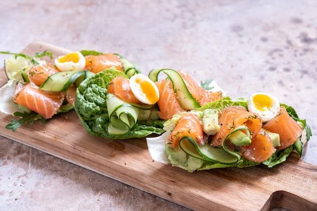 Mit salat umwickelter räucherlachs-tacos mit frischen gurken-, avocado- und wachteleiern