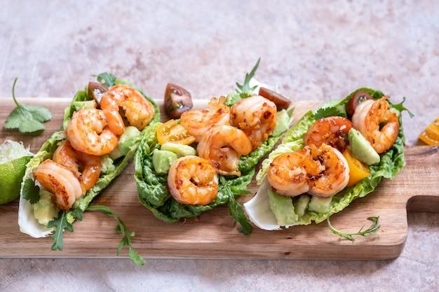 Mit salat umwickelter shrimps-tacos mit frischen tomaten, avocado und limette