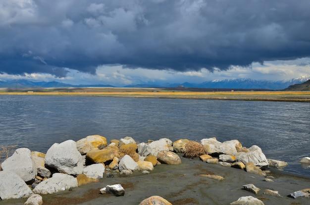 Mit salz bedeckte steine vor dem hintergrund eines salzsees und regenwolken. großer salzsee in utah, usa