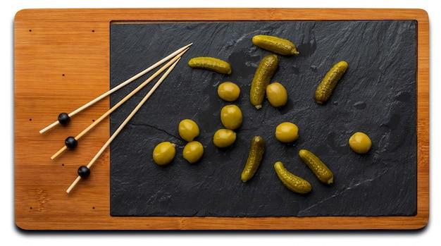 Mit sardellen und eingelegten essiggurken gefüllte oliven. auf holzbrett und schwarzem schiefer. draufsicht.