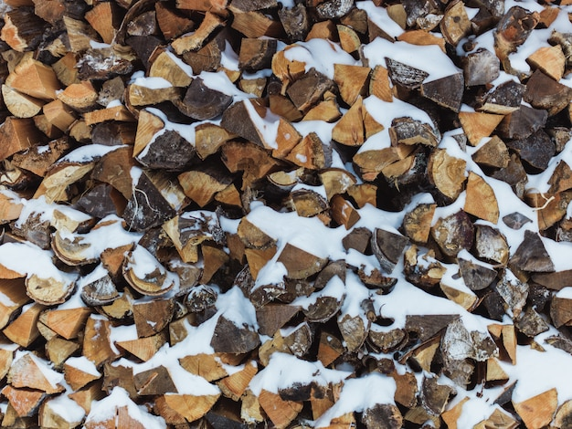 Mit schnee bedeckter holzhaufen - ideal für eine kühle oder tapete