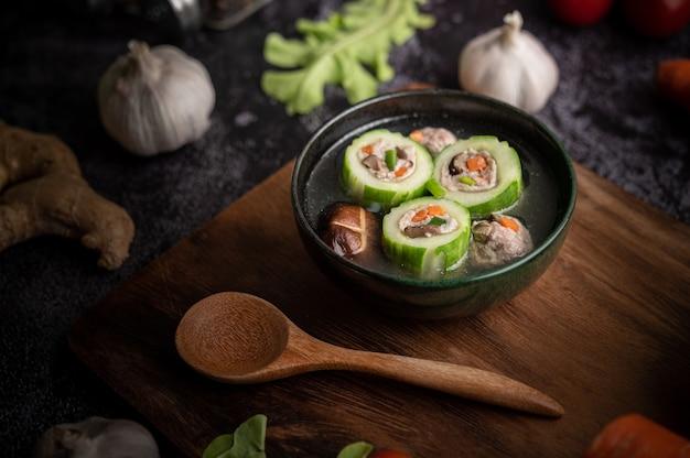 Mit schweinefleisch gefüllte gurkensuppe mit karotten, gehackten frühlingszwiebeln, shiitake-pilzen und knoblauch