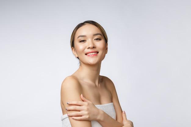 Mit seiten versehenes porträt des asiatischen schönen lächelnden mädchens mit dem kurzen haar, das ihre gesunde haut zeigt