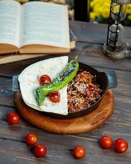 Mit sesam garniertes teriyaki-huhn, serviert mit gegrillten fladenbrot-tomaten und pfeffer