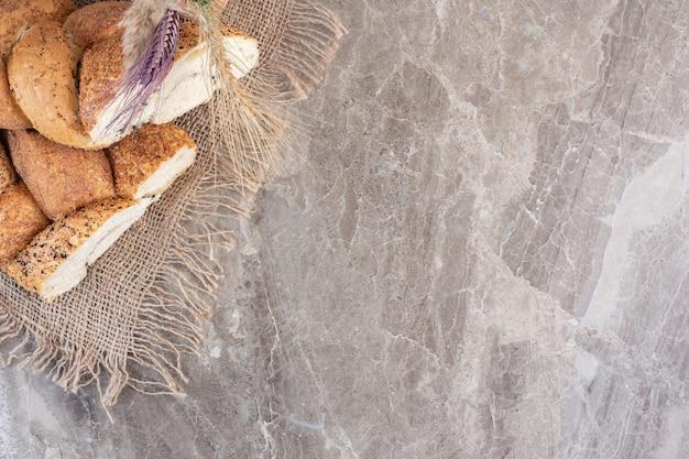 Mit sesam überzogene, geschnittene brotlaibe mit weizenstielen auf marmor.