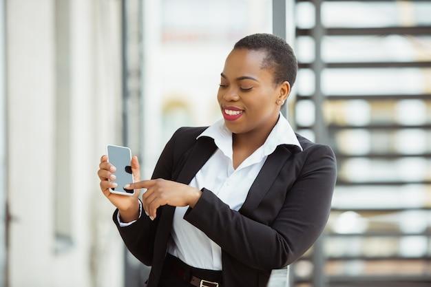 Mit smartphone afroamerikanische geschäftsfrau in bürokleidung lächelnd