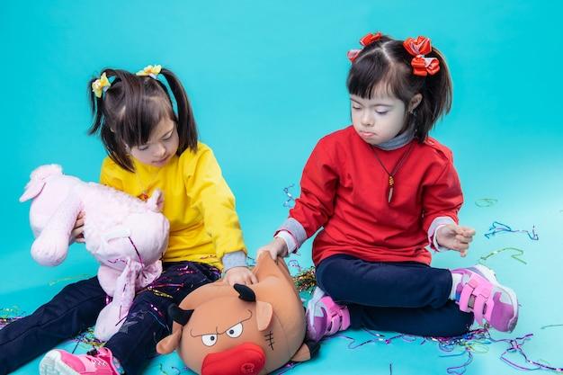 Mit spielzeug spielen. ansprechende zwillinge, die zeit zusammen mit plüschtieren verbringen, während sie auf dem boden sitzen