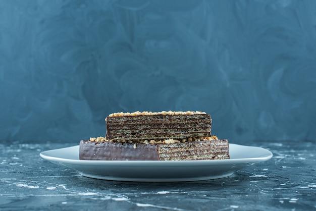 Mit süßer schokolade überzogene waffel auf einem teller, auf dem blauen hintergrund.