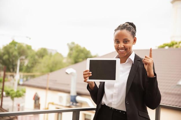 Mit tablet nach oben zeigen. afroamerikanische geschäftsfrau in bürokleidung lächelnd, sieht selbstbewusst und glücklich aus. konzept für finanzen, wirtschaft, gleichstellung und menschenrechte. schönes junges modell, erfolgreich.
