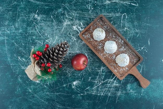 Mit vanille überzogene kuchen auf einem kleinen tablett, ein apfel und eine weihnachtsverzierung auf blau.