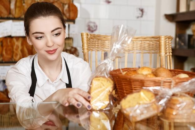 Mit vergnügen arbeiten. schuss einer hübschen bäckerin, die schaufenster in ihrem laden verziert und fröhlich lächelt
