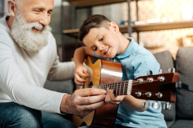 Mit vergnügen unterrichten. fröhlicher älterer mann, der seinem geliebten enkel beibringt, wie man gitarren- und schlagakkorde spielt, während er glücklich lächelt