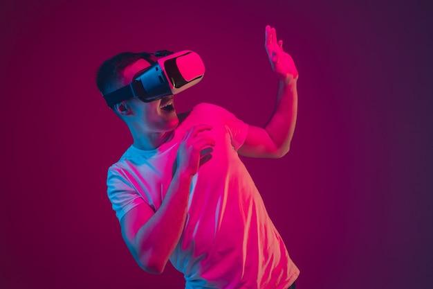 Mit vr spielen, filmen, fahren. porträt des kaukasischen mannes isoliert auf rosa-violetter wand im neonlicht. männliches model mit geräten. konzept der menschlichen emotionen, gesichtsausdruck, verkauf, anzeige.