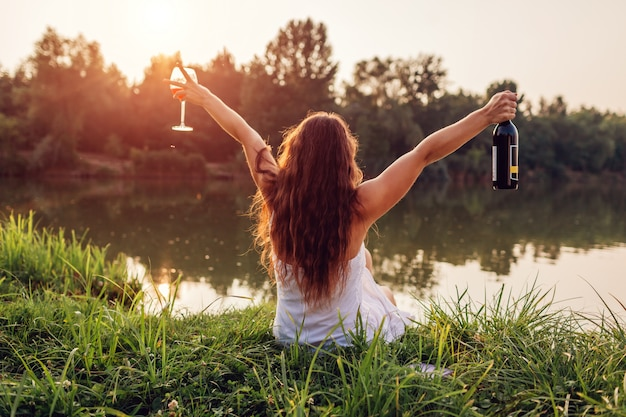 Mit wein abkühlen. frau, die glas wein auf flussbank bei dem sonnenuntergang anhebt arme genießt und frei und glücklich sich fühlt.