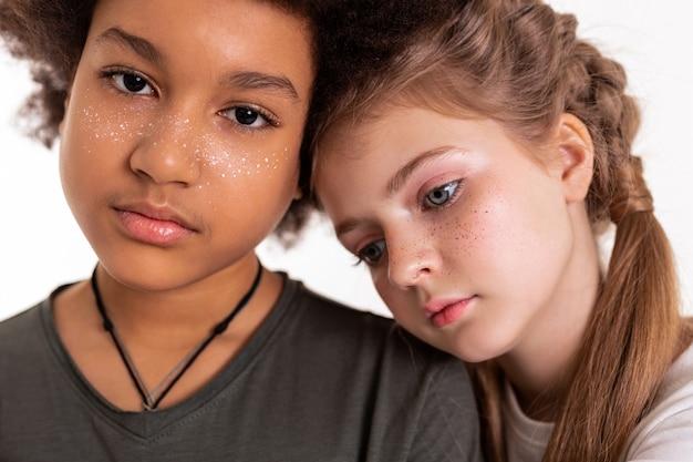 Mit weißem hintergrund. hübsche junge kinder, die ihre sommersprossen aufgemalt haben und dicht beieinander stehen