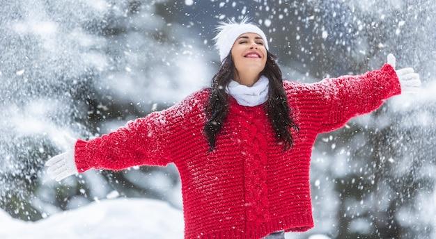 Mit weit geöffneten armen genießt die frau in rotem pullover, weißen handschuhen, schal und mütze an einem verschneiten wintertag frische luft.