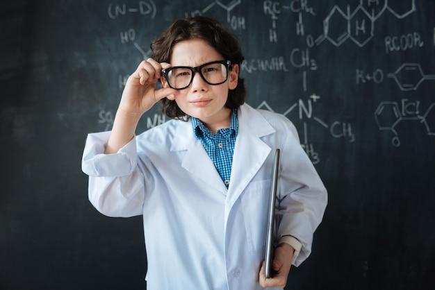 Mit zuversicht in die zukunft schauen. brainy sah gut aus, als ein forscher in der nähe der tafel im labor stand, während er den chemieunterricht genoss und seine brille berührte