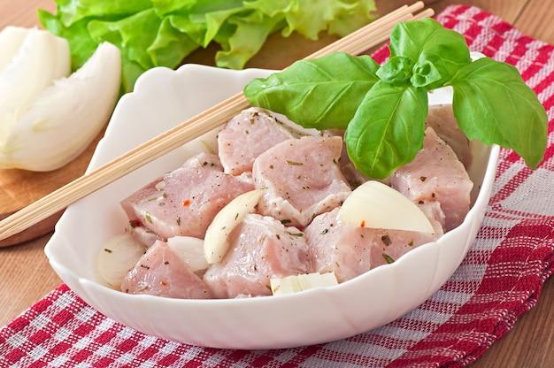 Mit zwiebeln und kräutern marinierte fleischstücke zum grillen zubereitet