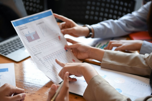 Mitarbeiter analysieren daten. sie verwenden ihre hände auf diagramme.