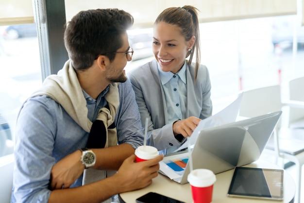 Mitarbeiter arbeiten am projekt, während sie im café sitzen. auf dem schreibtisch laptop, tablet und einwegbecher mit kaffee.