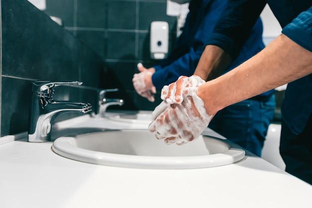 Mitarbeiter aus der nähe waschen sich gründlich die hände