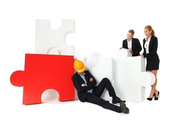 Mitarbeiter betrachten müden vorarbeiter, der in der nähe des puzzles schläft, isoliert auf weißem hintergrund