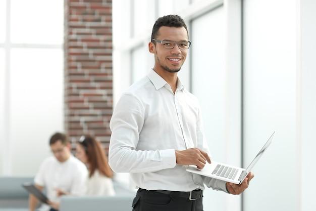 Mitarbeiter, der auf einem laptop steht, der im büro steht.